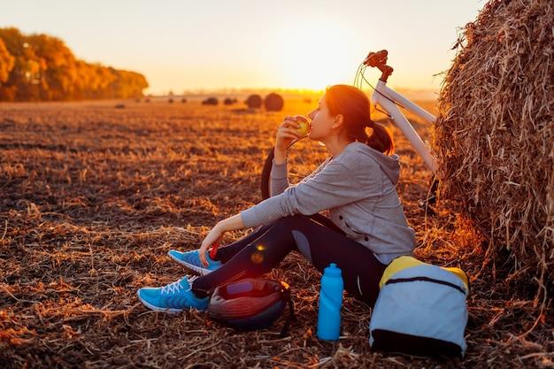 Młody rowerzysta po odpoczynku po przejażdżce w jesiennym polu o zachodzie słońca. kobieta je jabłko przy stogu siana