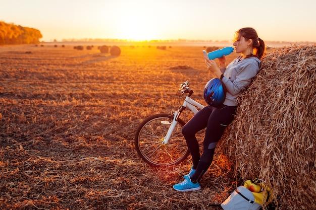 Młody rowerzysta po odpoczynku po przejażdżce w jesiennym polu o zachodzie słońca. kobieta pije wodę przy stogu siana i szuka drogi przez telefon