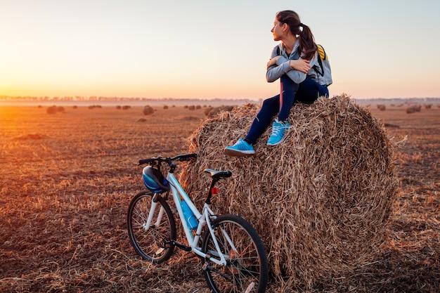 Młody rowerzysta po odpoczynku po przejażdżce w jesiennym polu o zachodzie słońca. kobieta podziwia widok siedząc na stogu siana. koncepcja rekreacji sportowej