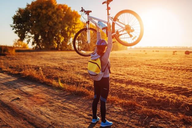 Młody rowerzysta podnosząc swój rower w jesień pole o zachodzie słońca. szczęśliwa kobieta świętuje zwycięstwo trzymając rower w ręce.