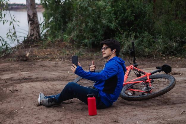 Młody rowerzysta robi sobie selfie, odpoczywa na ziemi obok swojego roweru