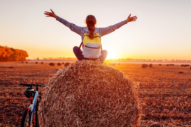 Młody rowerzysta siedzący na stogu siana z podniesionymi i otwartymi ramionami po przejażdżce. kobieta o odpoczynku w jesiennym polu podziwiając widok. sportowy styl życia