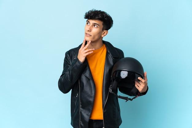 Młody rowerzysta trzymając kask motocyklowy