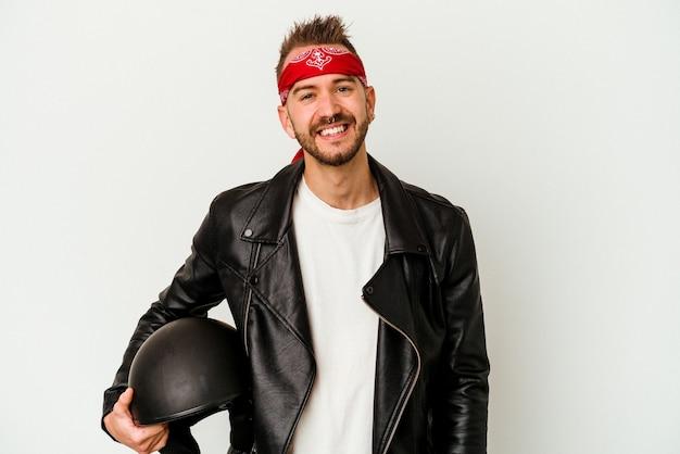 Młody rowerzysta wytatuowany kaukaski mężczyzna trzyma kask na białym tle na białej ścianie szczęśliwy, uśmiechnięty i wesoły.
