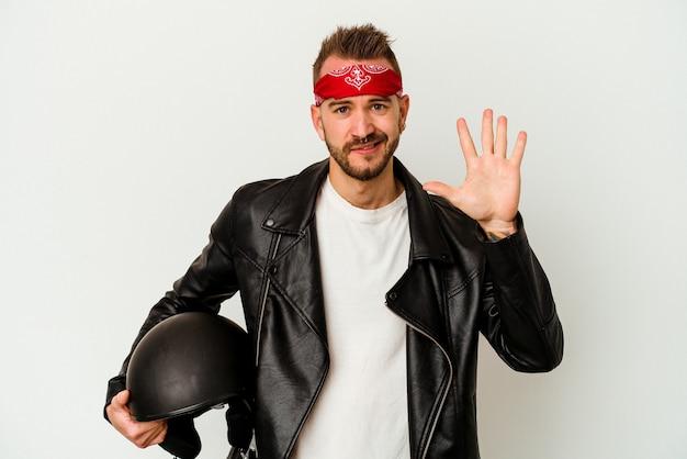 Młody rowerzysta wytatuowany kaukaski mężczyzna trzyma kask na białym tle na białej ścianie uśmiechnięty wesoły pokazując numer pięć palcami.