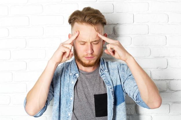 Młody rozczarowany mężczyzna zakrywa twarz