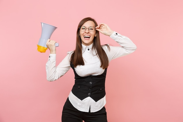 Młody roześmiany radosny biznes kobieta w czarnym garniturze, koszuli i okularach trzymając megafon na białym tle na pastelowym różowym tle. szefowa. koncepcja bogactwa kariery osiągnięcia. skopiuj miejsce na reklamę.