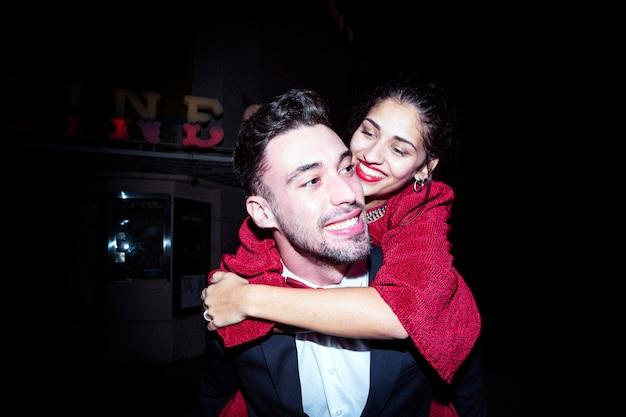 Młody rozochocony facet trzyma dalej tylną atrakcyjną uśmiechniętą damę
