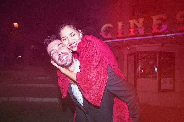 Młody rozochocony facet trzyma dalej tylną piękną uśmiechniętą damę przy nocą