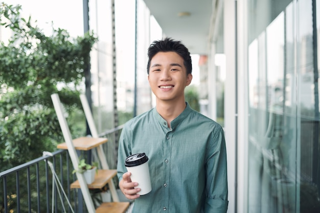 Młody rozważny student stojący na ulicy miasta z papierowym kubkiem kawy na wynos