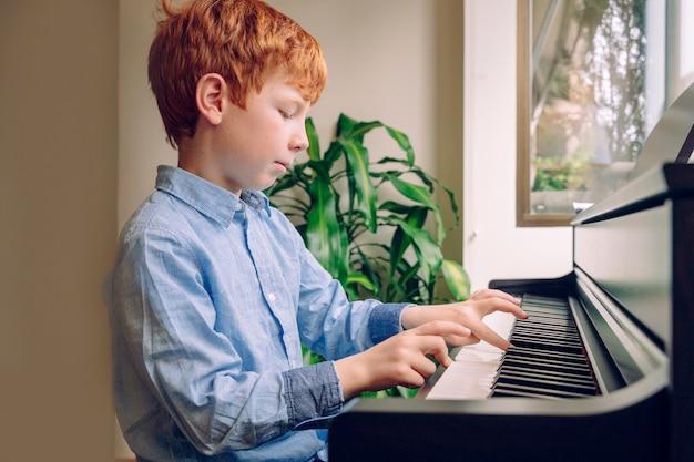 Młody rudowłosy dzieciak gra na pianinie. chłopiec ćwiczy lekcje muzyki na klawiaturze w domu. studiuj i ucz się koncepcji kariery muzycznej. styl życia rodziny z dziećmi. działania edukacyjne w domu.