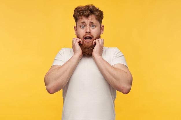 Młody rudowłosy mężczyzna z dużą brodą i żółtym wystraszonym wyrazem twarzy