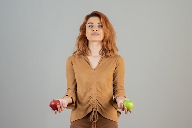 Młody rudowłosy pewnie trzyma ekologiczne świeże jabłka.