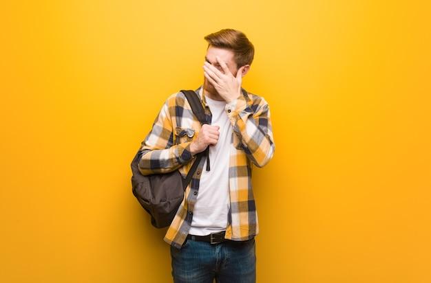 Młody rudowłosy student zawstydzony i jednocześnie śmiejący się