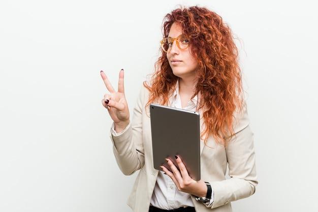 Młody rudy biznes kaukaski kobieta trzyma tabletkę pokazując numer dwa palcami.