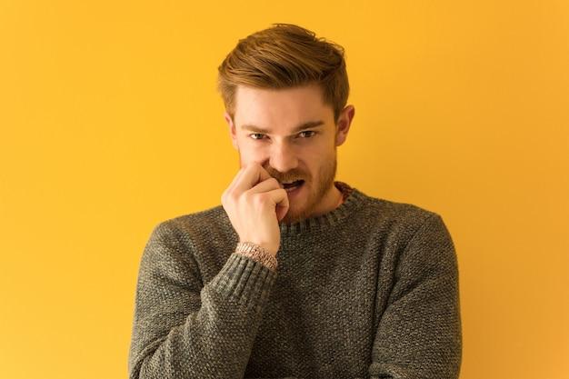 Młody rudy człowiek twarz zbliżenie gryzienie paznokci, nerwowy i bardzo niespokojny