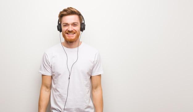 Młody rudy człowiek wesoły z wielkim uśmiechem. słuchanie muzyki przez słuchawki.