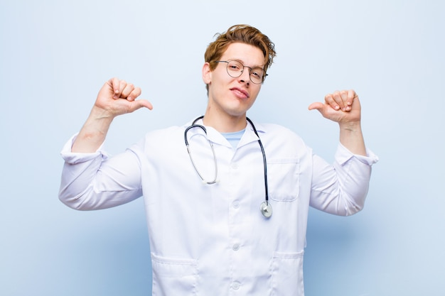 Młody rudy lekarz czuje się dumny, arogancki i pewny siebie, wygląda na zadowolonego i odnoszącego sukcesy, wskazując na siebie
