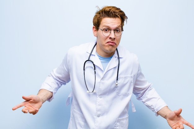 Młody rudy lekarz czuje się nieświadomy i zdezorientowany, nie mając pojęcia, całkowicie zaskoczony głupim lub głupim spojrzeniem na niebiesko