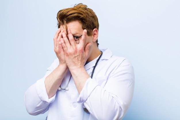 Młody rudy lekarz czuje się przestraszony lub zawstydzony, zerkając lub szpiegując oczy na wpół pokryte rękami na niebieskiej ścianie