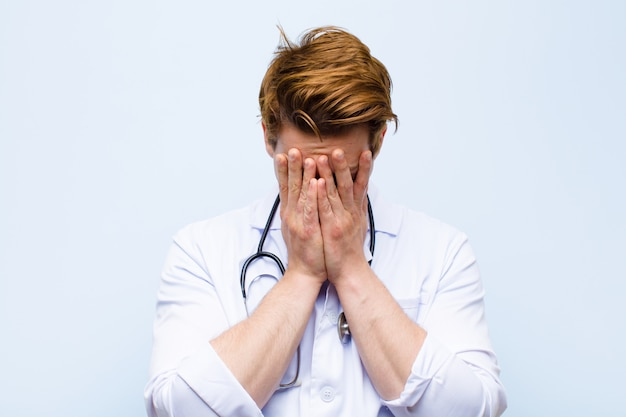 Młody rudy lekarz czuje się smutny, sfrustrowany, zdenerwowany i przygnębiony, zakrywa twarz obiema rękami, płacze niebieską ścianę