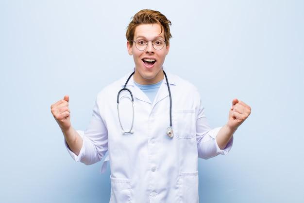 Młody rudy lekarz czuje się szczęśliwy, zaskoczony i dumny, krzyczy i świętuje sukces z wielkim uśmiechem