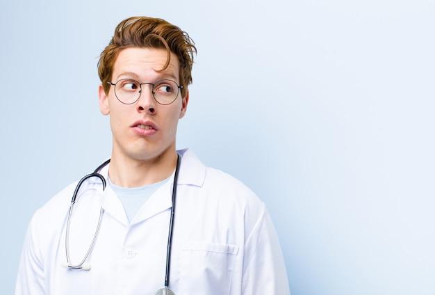 Młody rudy lekarz czuje się zszokowany, zaskoczony i zaskoczony, patrząc w bok z otwartymi ustami