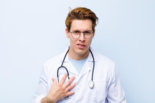 Młody rudy lekarz czuje się zszokowany, zdziwiony i zaskoczony, z ręką na piersi i otwartymi ustami, mówiąc, kto, ja? niebieska ściana