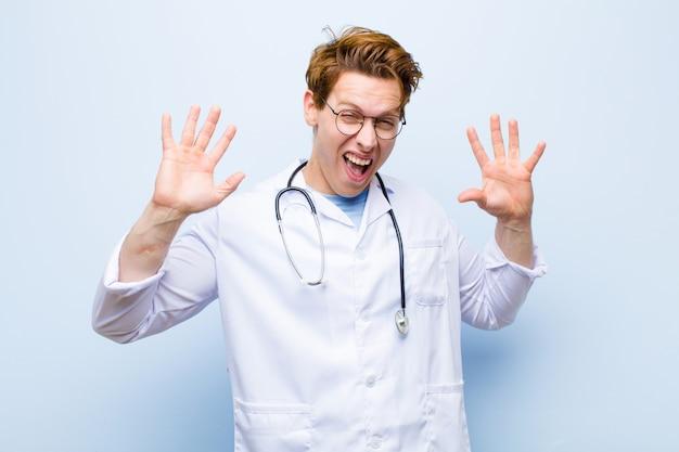 Młody rudy lekarz krzyczy z paniki lub gniewu, zszokowany, przerażony lub wściekły, z rękami obok głowy na niebieskiej ścianie
