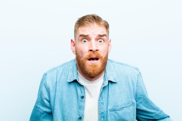 Młody rudy mężczyzna czuje się przerażony i zszokowany, z szeroko otwartymi ustami z zaskoczenia na miękkiej niebieskiej ścianie