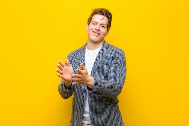 Młody rudy mężczyzna czuje się szczęśliwy i udany, uśmiecha się i klaszcze w dłonie, gratulując oklaskami pomarańczy