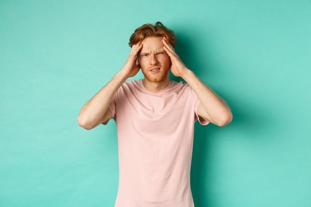 Młody rudy mężczyzna dotyka głowy i szuka zawrotów głowy, czuje ból głowy lub migrenę, stoi w koszulce na miętowym tle.
