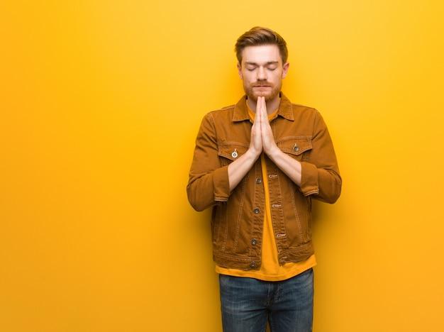 Młody rudy mężczyzna modli się bardzo szczęśliwy i pewny siebie