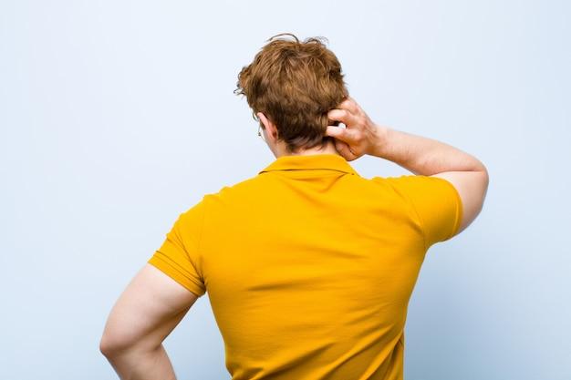 Młody rudy mężczyzna myśli lub wątpi, drapie się po głowie, czuje się zdziwiony i zdezorientowany, widok z tyłu lub z tyłu na niebieską ścianę