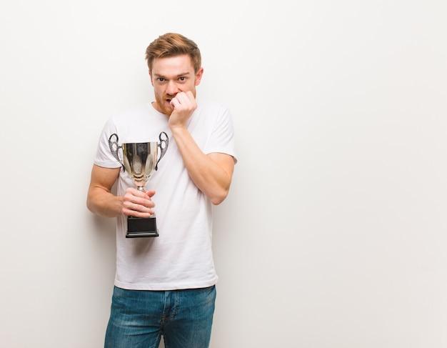 Młody rudy mężczyzna obgryzający paznokcie, nerwowy i bardzo niespokojny. trzymać trofeum.