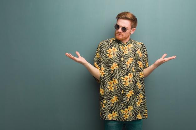 Młody rudy mężczyzna ubrany w egzotyczne letnie ubrania zdezorientowany i wątpliwy