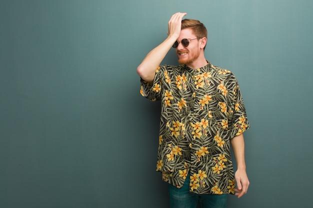 Młody rudy mężczyzna w egzotycznych letnich ubraniach zapomina, zdaje sobie sprawę z czegoś