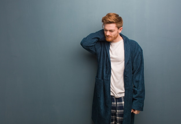 Młody rudy mężczyzna w piżamie cierpi ból szyi