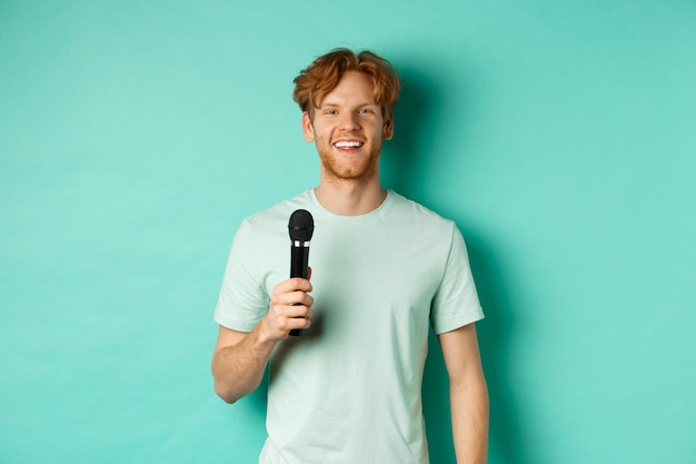 Młody rudy mężczyzna z brodą, ubrany w t-shirt, trzymający mikrofon i przemawiający, śpiewający karaoke, stojący nad miętowym tłem.