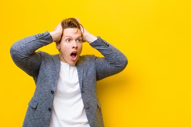 Młody rudy mężczyzna z otwartymi ustami, wyglądający na przerażonego i zszokowanego z powodu strasznego błędu, podnoszący ręce do głowy na pomarańczowo