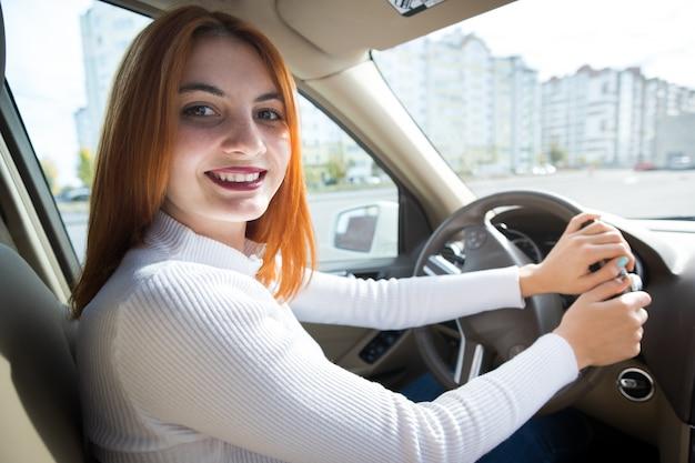 Młody rudzielec kobiety kierowca za kołem jedzie samochód ono uśmiecha się szczęśliwie.