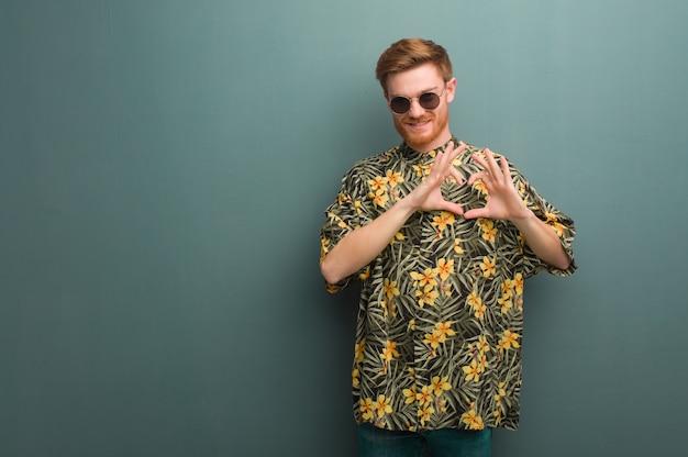 Młody rudzielec mężczyzna jest ubranym egzotycznych lato ubrania robi kierowemu kształtowi z rękami