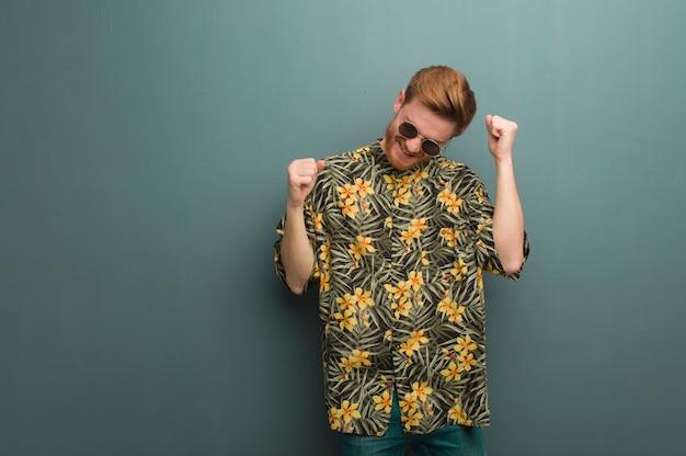 Młody rudzielec mężczyzna jest ubranym egzotycznych lato ubrania tanczy zabawę i ma