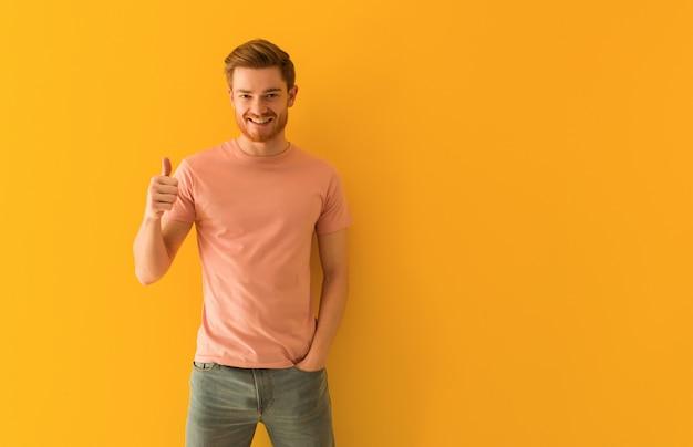 Młody rudzielec mężczyzna ono uśmiecha się i podnosi kciuk up