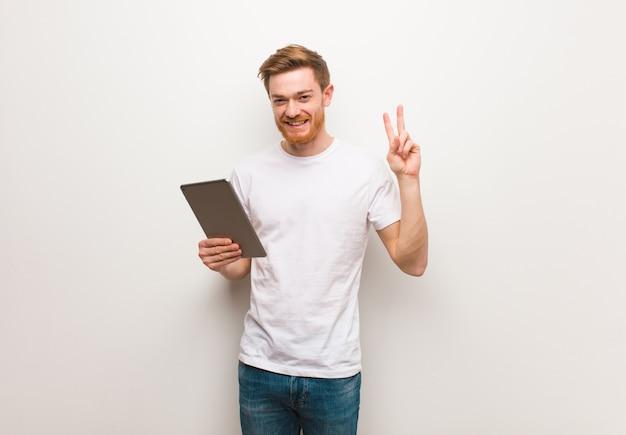 Młody rudzielec mężczyzna pokazuje numer dwa. trzymać tablet.