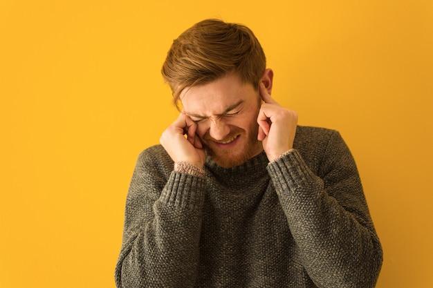 Młody rudzielec mężczyzna twarzy zbliżenia nakrywkowi ucho z rękami