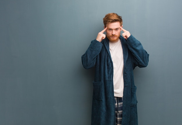 Młody rudzielec mężczyzna w piżamie robi koncentracyjnemu gestowi