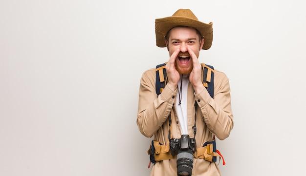 Młody rudzielec odkrywca krzyczy coś szczęśliwego do przodu. trzymanie aparatu