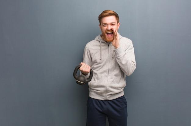 Młody rudzielec sprawności fizycznej mężczyzna krzyczy coś szczęśliwego z przodu. trzymać hantle.