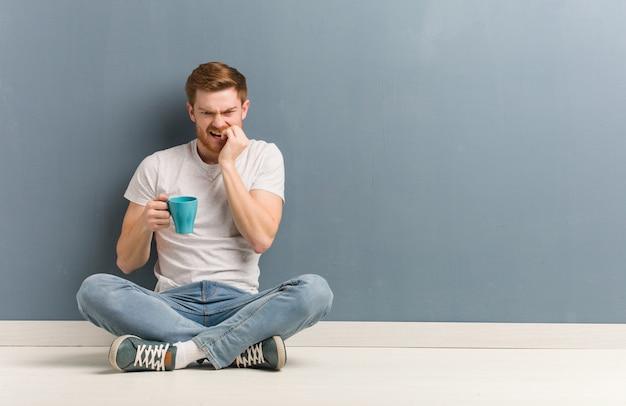 Młody rudzielec studencki mężczyzna siedzi na podłodze obgryzać paznokcie, nerwowy i bardzo niespokojny